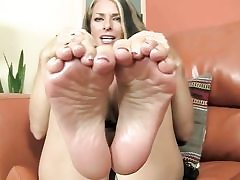 Sweet looking stunner is revealing her feet and is ready to give footjob