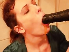 Nasty slut is getting face fucked with a thick black cord on